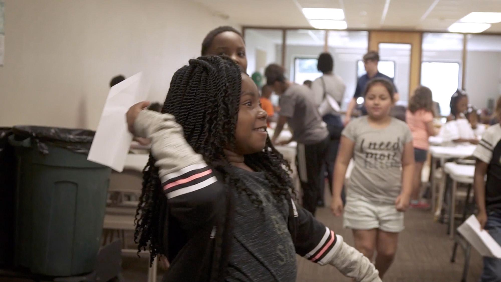 Student throwing paper plane in University of West Florida Graduate's Inertia program