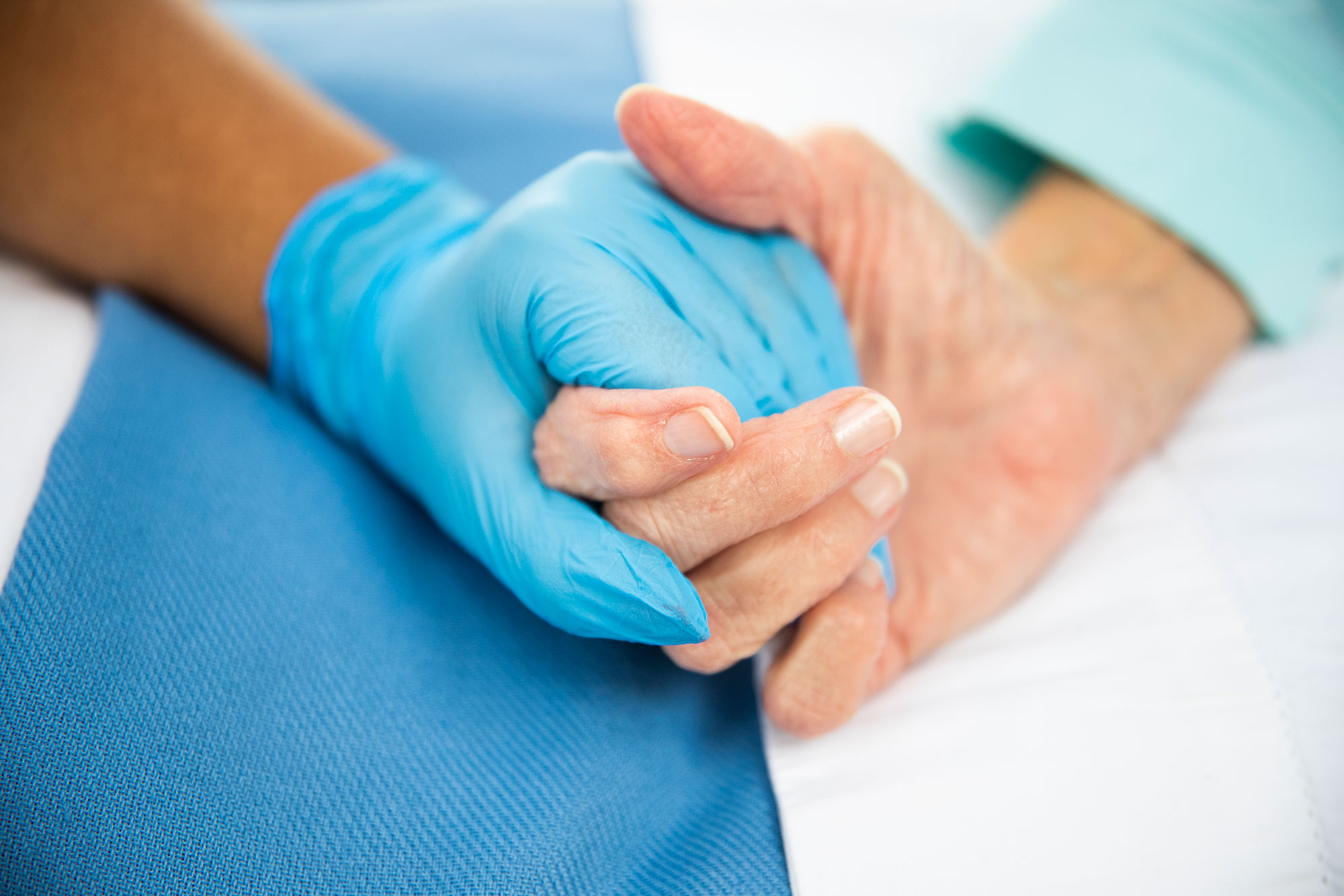 Close of Praise's gloved hands holding what appears to be the hands of a patient. Caption